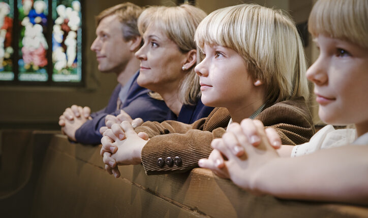 Family Kneeling and Praying in Church