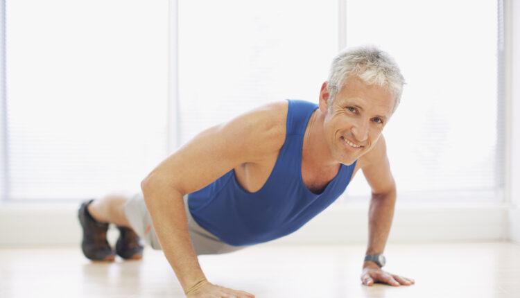 Portrait of smiling man doing push-ups in fitness studio